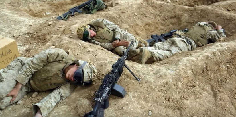 military soliders lying in bunkers with backpain